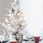 Exciting Silver And White Table Top Christmas Tree In Small Size With Star Ornaments In The Silver Pot Placed Near Red Candle And White Plates And Wine Glasses