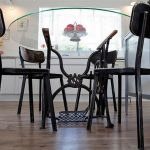 exclusibe black chairs design for dining set with glass round table on wooden floor with chandelier and glass window