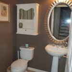 genius brown bathroom color trend with freestanding vanity and sun framed wall mirror and toiletries cabinet