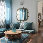 gorgeous interior desgn with turquoise floor seating idea and round wooden coffee table with blue patterned area rug and wooden floor and sheer curtain