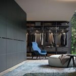 gorgeous interior with open concept and blue chair and wall storage for clothes and glass window and white pouff