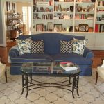gorgeous navy blue slip cover for sectional design with colorful cushions and white chairs and glass coffee table