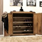 gorgeous rustic shoe storage in the entry with slapped doors and wall pictures and creamy area rug