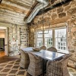 gorgeous rustic stone house interior design with stone wall and rattan dining set and glossy dining table and brown patterned area rug and wooden floor