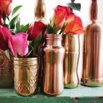 gorgeous spring mood decoration for interior with golden vases on green table with various flowers