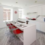 Gorgeous White Kitchen Interior Design With Bar And Red Stools And Gray Painted Flooring And Glass Window