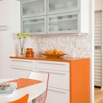gorgeous white orange kitchen design with wooden floor and stunning wallpaper backsplash and orange breakfast nook