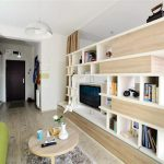 great apartment design with woode bookshelves and TV console and wooden floor and gray rug and round wooden coffee table