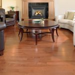 hardwood floor vs laminate in living room area decorated with round wooden table and brown leather chairs and modern sofa plus awesome fireplace