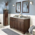 images of bathroom vanities and cabinets in dark finish with solid granite countertop and two traditional framed mirror on grey wall plus striking wall sconces