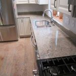 kashmir white granite countertops with white cabinets and stainless steel kitchen appliances and wooden floor