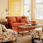 livable living room design with wooden coffee table and orange sofa and floral patterned arm chairs and area rug and glass window