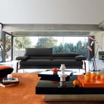 livable modern living room design with gray sofa and orange couch and modern coffee tbale with unique flooring and area rug