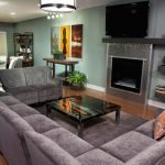 Lovable Purple Long Sectional Sofa Design With Brown Glossy Wooden Coffee Table With Orange Cushions Before Fireplace And Wooden Floor And Wall Shelves