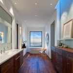 luxurious bathroom trend design with wooden floor and wooden vanity and wall mirror and celing lamos and large glass window