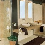 luxurious creamy contemporay bathroom with brown rug and white round bathtub and creamy curtain and wall mirrors and floating vanity and indoor plant