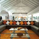 luxurious interior design with long black sectional sofa design with colorful cushions in white orange and yellow with glass coffee table and vaulted ceiling