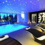 luxurious modern house swimming pool design with gorgeous blue lighting on the ceiling with sophisticated pool chairs with sexy design
