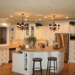luxurious small kitchen design with white cabinetry and white island with black stools and wooden floor and chandelier