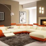 luxurious sofa in the living room with white and orange detail on gray area rug with curved floor lamp and gray siding paint
