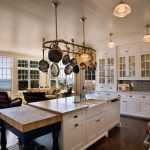 mesmerizing kitchen ideas with pot rack with lights decorated on the top of kitchen island and black subway tile backsplash and white cabinet and brown hardwood floor