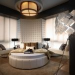modern and luxurious bedroom design with white bold round bed with creamy sheet and giant ceiling lamps and unique floor lamps and upholstered wall