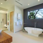 modern bath with purple painted wall and white bathtub and glass table and wooden floor and vanity