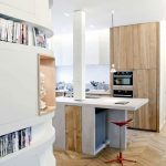 modern white small kitchen design with wooden cbainet and white isladn with red stool and chevron wooden floor and bookshelves