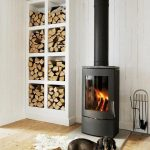 Nordic Design Wood Stove And White Firewood Storage With Eight Square Box Near The Black Fireplace On The Wooden Floor And Wooden Wall