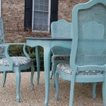 outdoor dining area with turquoise cane back dining chair with grey patterned upholstery and wooden dining table