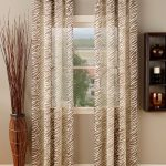 playful patterned sheer curtain design with dried plants and gray painted wall and floating shelves