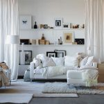 posh white interior living room idea with white sectional sofa and white faux fluffy rug idea and glass window and wall unit