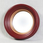 red frame small convex mirror mounted on white wall