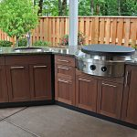 simple and neutral outdoor kitchen design with wooden cbainet and marble countertop and stove top and large tile flooring and wooden fence