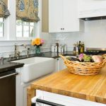 simple and small kitchen design with white dominant color with white beige island and gray blue patterned curtain