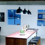 simple kitchen design with long narrow wooden island with black vault pendants and black leather scandinavian stools