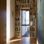 simple natural wooden floor in the interior with wooden sliding door and wooden built in bookshelves on door frame