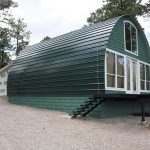 small and awesome quonset hut homes in appealing design with green painted wall and glass windows and door