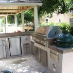 small outdoor kitchen design with dull white cabinet with modern kicthenette and pergola and stone flooring