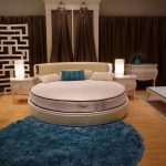 smple round bed design with blue pillow and furry area rug and wooden floor and turquoise chair