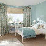 soft blue bedroom design with gray sheer curtain on glass window with white bedding and blue blanket and wooden floor