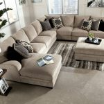 soft brown fabric long sectional sofa with chaise in one side together with decorative cushion and wooden end table plus ottoman coffee table