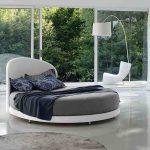 spacious bedroom design with open plan and white chair and floor lamp and gray white round bed with black sheet