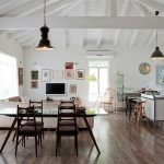 spacious interior design of a house with wooden floor and united living space and wooden dining table and vintage black pendants