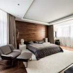 stunning apartment bedroom design with gray bedding and brown curtain and glass window and wooden floor ad reclining chair