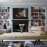 stunning bright white interior with open plan and creamy velvet sofa and wooden floor and built in bookshelves and table lamp