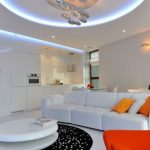 stunning interior with suspended ceiling and round area rug and white sofa and orange accent pillow