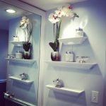 Stunning Modern Bathroom Idea With Large Wall Mirror And Molded Bathroom Shelves In White With Orchid Decoration And Modern Lighting