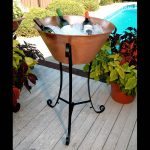 stunning tan baverage tub with stand with scrolled black iron legs on wooden deck aside pool
