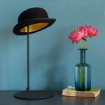 stylish hat shaped shaded unusual table lamp design on wooden table with flower decoration
